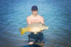 Pesca de la carpa Pescador joven que sostiene una carpa común grande en el lago fotos de archivo