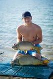 Pesca de la carpa Pescador sonriente joven con dos carpas comunes foto de archivo