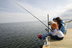 Pesca de la familia con el perro Fotos de archivo libres de regalías