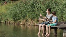 Pesca de la familia con las barras por la charca en verano almacen de metraje de vídeo