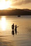 Pesca de la familia del padre y del hijo en la puesta del sol Fotografía de archivo