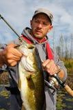 Pesca de la lubina del hombre Fotografía de archivo libre de regalías
