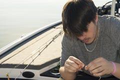 Pesca de la lubina en barco bajo en el lago Foto de archivo