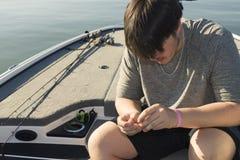Pesca de la lubina en barco bajo en el lago Fotos de archivo