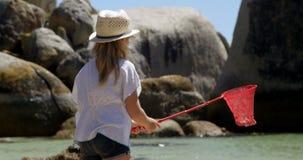 Pesca de la muchacha con la red en la playa 4k almacen de metraje de vídeo