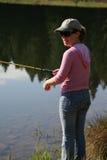 Pesca de la mujer en el lago Foto de archivo libre de regalías