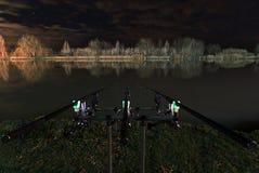 Pesca de la noche, carpa Roces, cierre encima de las cañas de pescar, reflexión de Nightscape en el lago foto de archivo