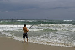 Pesca de la orilla del hombre durante tormenta Foto de archivo libre de regalías