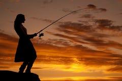 Pesca de la puesta del sol de la mujer foto de archivo libre de regalías