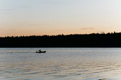 Pesca de la silueta en un pequeño lago imagen de archivo libre de regalías