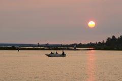 Pesca de lago en la puesta del sol Fotografía de archivo