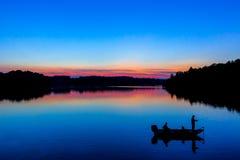 Pesca de lago en la puesta del sol Imágenes de archivo libres de regalías