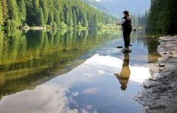 Pesca de mosca de la mujer en un lago foto de archivo