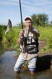 Pesca de mosca del pescador en un lago Foto de archivo