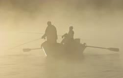 Pesca de mosca em um barco de tração na névoa imagens de stock royalty free