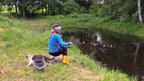 Pesca de pescador na lagoa rural, espera com fome de Gir do gato para peixes filme