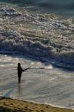 Pesca de resaca del hombre en el océano Imágenes de archivo libres de regalías