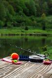 Pesca dei rifornimenti su una tavola vicino ad un lago Fotografia Stock