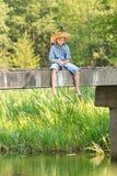 Pesca del adolescente con la barra en el puente Imagen de archivo libre de regalías