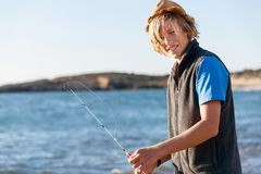 Pesca del adolescente en el mar Imagen de archivo libre de regalías