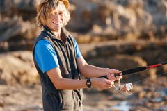Pesca del adolescente en el mar Foto de archivo libre de regalías