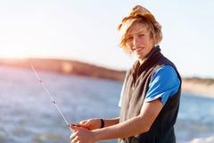 Pesca del adolescente en el mar Fotos de archivo libres de regalías