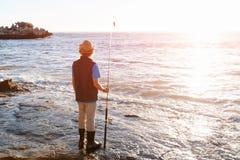 Pesca del adolescente en el mar Imagen de archivo