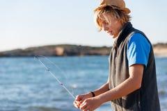 Pesca del adolescente en el mar Fotografía de archivo libre de regalías