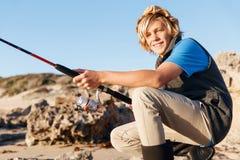 Pesca del adolescente en el mar Foto de archivo