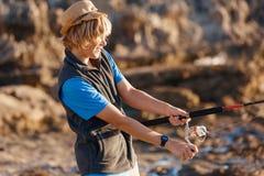 Pesca del adolescente en el mar Fotos de archivo