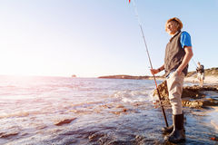 Pesca del adolescente en el mar Fotografía de archivo