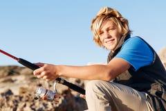 Pesca del adolescente en el mar Imagenes de archivo