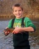 Pesca del bambino - tenere una trota iridea fotografia stock