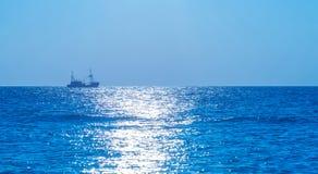 Pesca del barco rastreador en el mar en la puesta del sol Imagenes de archivo
