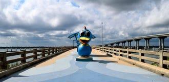 Pesca del embarcadero con el fondo de la estatua del pato fotos de archivo libres de regalías