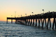 Pesca del embarcadero en el Golfo de México en la puesta del sol fotos de archivo