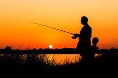 Pesca del figlio e del padre nel fiume Fotografia Stock