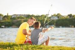 Pesca del figlio e del papà dalla riva immagine stock
