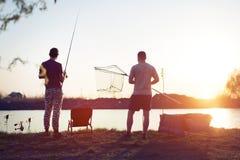 Pesca del giovane su un lago al tramonto ed all'hobby godere fotografia stock libera da diritti