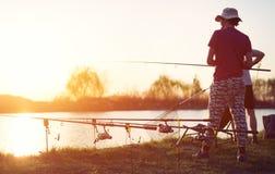 Pesca del giovane su un lago al tramonto ed all'hobby godere fotografia stock