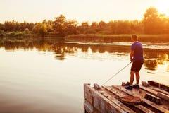 Pesca del giovane sul fiume che sta sul ponte al tramonto Fiserman felice che gode dell'hobby fotografia stock libera da diritti