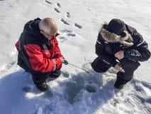 Pesca del hielo en el lago Inari Imagen de archivo