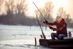 Pesca del hielo en pescados sonrientes de la captura del pescador del lago congelado fotos de archivo