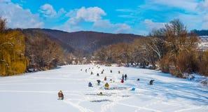 Pesca del hielo en un río congelado Imágenes de archivo libres de regalías