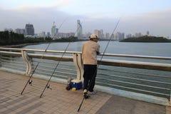 Pesca del hombre con tres cañas de pescar Imagenes de archivo
