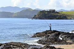 Pesca del hombre de una roca Imágenes de archivo libres de regalías