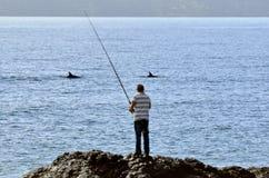 Pesca del hombre de una roca Fotografía de archivo