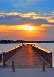 Pesca del hombre en el embarcadero en la puesta del sol Foto de archivo libre de regalías