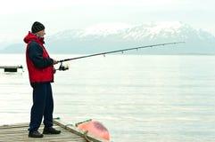 Pesca del hombre en el fiord Imagenes de archivo
