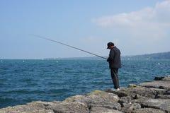 Pesca del hombre en el lago geneva Imágenes de archivo libres de regalías